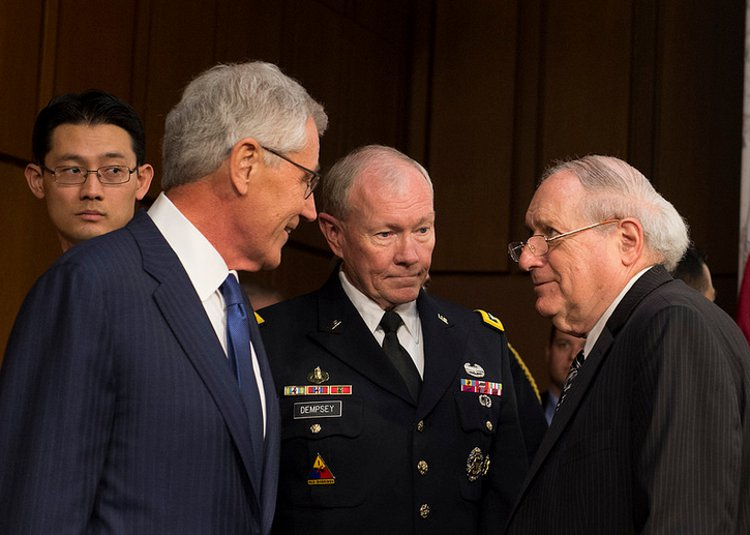 Secretary of Defense Chuck Hagel and Chairman of the Joint Chiefs of Staff Gen. Martin E. Dempsey talk with Sen. Carl Levin, Chairman of the Senate Armed Services Committee, before testifying before the Senate Armed Services Committee in Washington D.C. Sept. 16, 2014. President Barack H. Obama authorized military strikes in Syria to destroy, degrade, and defeat the terrorist group known as ISIS. Department of Defense Photo by Mass Communication Specialist 1st Class Daniel Hinton.